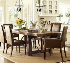 this featured inspiration room by pottery barn features a rustic wood and iron dining table classic leather parson s chairs and a unique glass light