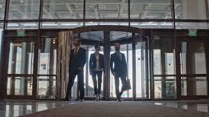 office corridor door glass. Businesswoman And Her Two Male Colleagues Entering Office Building Through Revolving Door Looking Around. Corridor Glass N