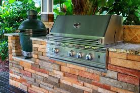 simple brick outdoor kitchen cabinet with smoker and stainless steel grill