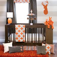 baby boy with modern large crib and modern bedding style