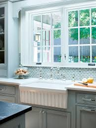 pretty french blue kitchen cabinetry and tiled backsplash fluted farmhouse sink vintage style faucets and white countertops