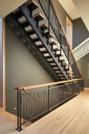 These striking steel and wood stairs have water jet-cut steel railings with  a pattern