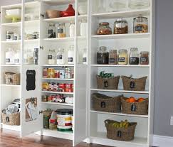 White bookshelves with glass doors used as a kitchen pantry