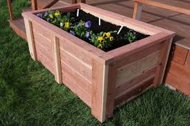 made from redwood it will withstand the elements this raised planter box is filled with flowers but i can see just about anything growing happily here