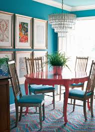 stylish dining room with blue wall color and furnished with pink round dining table paired with armless chairs over chandelier