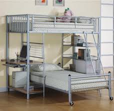 silver polished metal loft bunk bed with brown wooden desk and three tier open shelves on the other side as well as childrens beds with desks also