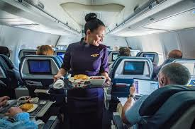 a delta flight attendant models the passport plum uniform while serving customers in flight