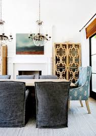 gorgeous dining room features a pair of paris flea market chandelier over a blond wood dining table lined with charcoal gray slipcovered dining chairs as