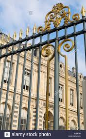 An ornate wrought iron fence protects the outside of the Louvre in