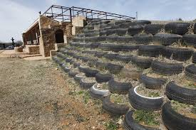 photo retaining wall made of old tires which will soon be covered with solar