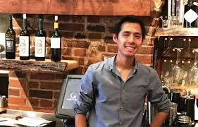 cevin lee poses behind the bar of his garden on grand restaurant