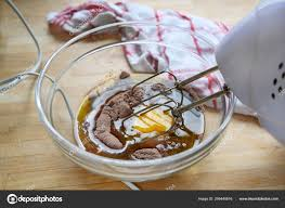 electric mixer in a glass bowl with cake dough of egg cocoa and flour on a wooden table with a kitchen towel baking concept selected focus photo by