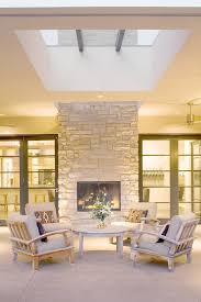 double sided fireplace indoor outdoor patio contemporary with armchairs concrete exterior skylight