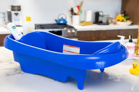 the first years sure comfort deluxe baby bath tub sitting atop a kitchen counter