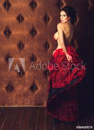 Sexy Beautiful Brunette Woman Dancing Striptease In Red Skirt With Naked Breasts On A Luxury Velvet Background Stock Photo