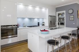 Sleek, contemporary white kitchen with pale blue glass splashback,  Caesarstone benchtops