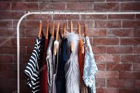 hangers with diffe female clothes on brick wall background stock photo