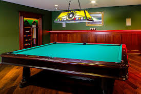 classic basement with yellow sterling billiard pool table light fixtures dark green wall painted