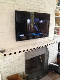 tv installation over a brick fireplace