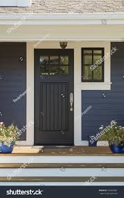 closed black front door with white surrounding door frame and blue siding