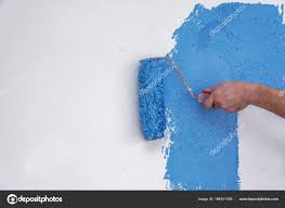 male hand painting wall in blue with paint roller stock photo
