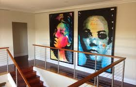 large framed artworks hanging from gallery picture rail cable system
