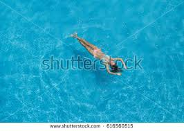 Top view of a girl in the swimming pool. Aerial view of slim woman floating