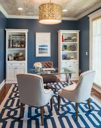 traditional home office with blue walls and rug together with nice pendant lighting on a wooden