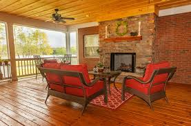 covered deck with outdoor fireplace with lake view