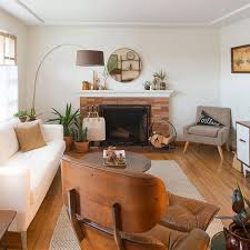 we love how light and bright this room feels the wood floor and dark leather armchair are perfectly balanced by the white walls and white couch