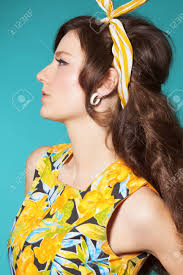 sixties fashion woman in colorful summer dress with retro hairstyle and makeup posing over cyan blue