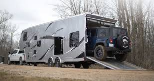 rear exterior of atc fifth wheel toy hauler laoding a jeep into garage