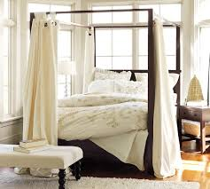 traditional bedroom completed with wooden diy canopy bed and white bedding beside oak nightstand and bench