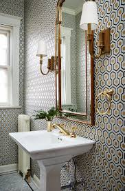 Fabulous powder room boasts walls clad in Cole & Son Hicks Hexagon Wallpaper  lined with a pedestal sink accented with a gold faucet kit below an arched  ...