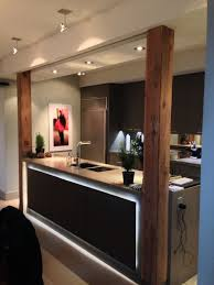 Custom kitchen and Millwork, cold rolled steel plate on face of island with  backlighting, reclaimed wood posts with cold rolled steel feet and ceiling  caps, ...
