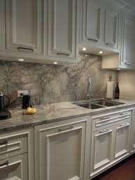 white cabinets and grey quartz counters and a backsplash for a stylish statement
