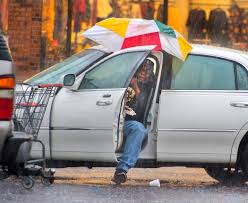 Harry Anderson tries to stay relatively dry as he maneuvers his umbrella  into position before slipping out of his car during a steady rainstorm,  Thursday, Dec 27, 2018, in Baton Rouge, La.