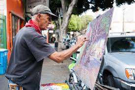 landscape painter and local artist works on an oil painting of 24th street scene on 24th street near york street in the mission district san francisco