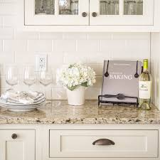 Venetian Gold Light Granite with off white subway tile and off white  cabinets. Cabinet color