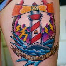 маяк с лентой и надписью тату на бедре у девушки добавлено иван