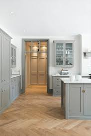 herringbone wood floor with gray shaker kitchen cabinets design by devol kitchens