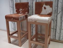 brown and white cowhide bar stool with back and brown wooden legs completed by footrest on