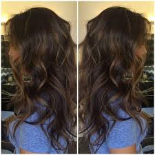 this model sports a head of golden brown highlights on her dark brown wavy hair