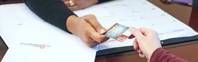 banker handing female customer a debit card