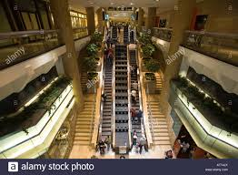 people on escalators. illinois chicago people riding escalators in water tower place mall interior fountain middle spurts of on