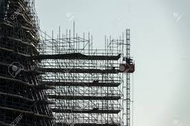 Silhouette Of Scaffolding Working At Building Construction Stock