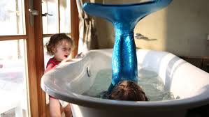 9 year old girl with fake mermaid costume and 2 year old toddler boy in bathtub