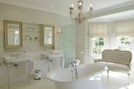 white french country bathroom with porcelain bathtub and subway wainscoting also brass chandelier