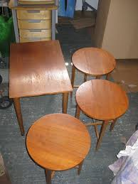nest of 4 wooden tables 1 rectangle table with 3 fold up round tables underneath