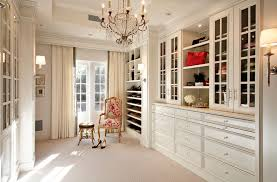luxury walk in closet with custom cabinets and window chair with small footstool